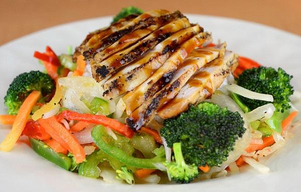 Pechuga de pollo con salsa sobre cama de verduras al ajillo