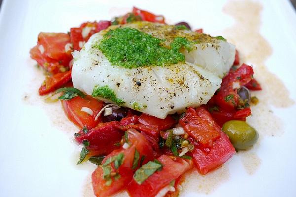 Bacalao con salsa verde sobre cama de pimientos asados y tomate